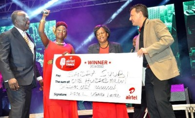 Airtel Uganda C.O.O Mr. Diego Javier hands over a cheque to Sandra Suubi and her family, the winner of the Airtel Trace Music Star competition during the Airtel Trace Music Star finals at Serena Hotel